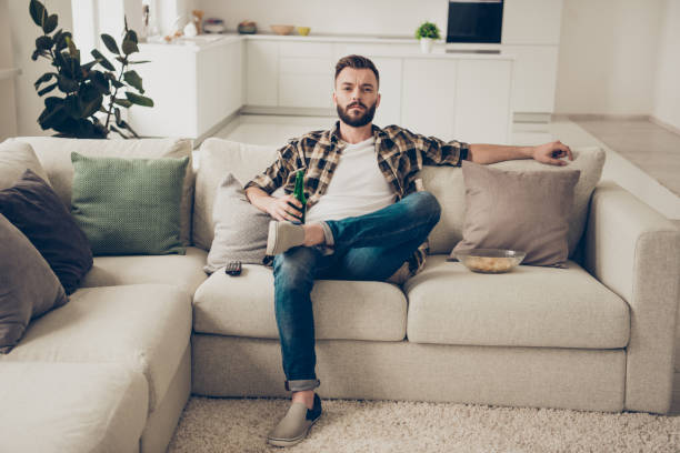 full length, legs, body, size portrait of handsome, bearded, nice, lovely, good-looking man in stylish trendy wear looks tv show siting on couch in large bright room - theatre full of people stage foto e immagini stock