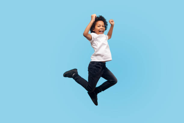 Full length, lively energetic little boy in T-shirt and denim jumping in air screaming with happiness Full length, lively energetic little boy in T-shirt and denim jumping in air screaming with happiness, child flying up, feeling inspired crazy and overjoyed. indoor studio shot, blue background mid air stock pictures, royalty-free photos & images