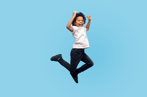 Full Length Lively Energetic Little Boy In Tshirt And Denim Jumping In Air Screaming With Happiness Stock Photo - Download Image Now
