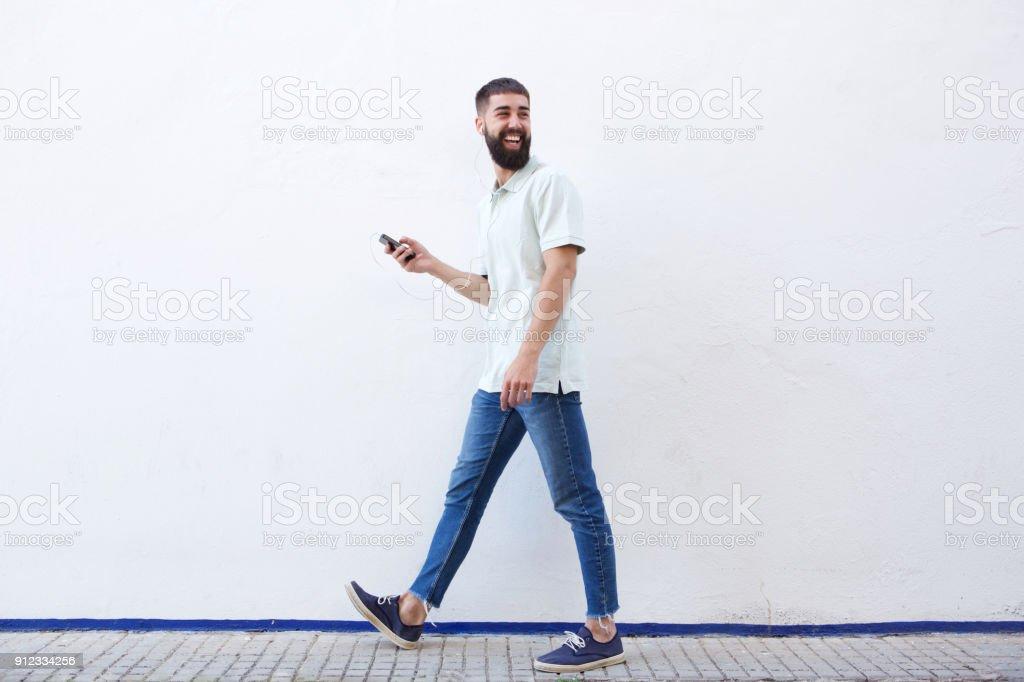 Homme de pleine longueur à pied et tenir téléphone mobile avec écouteurs - Photo