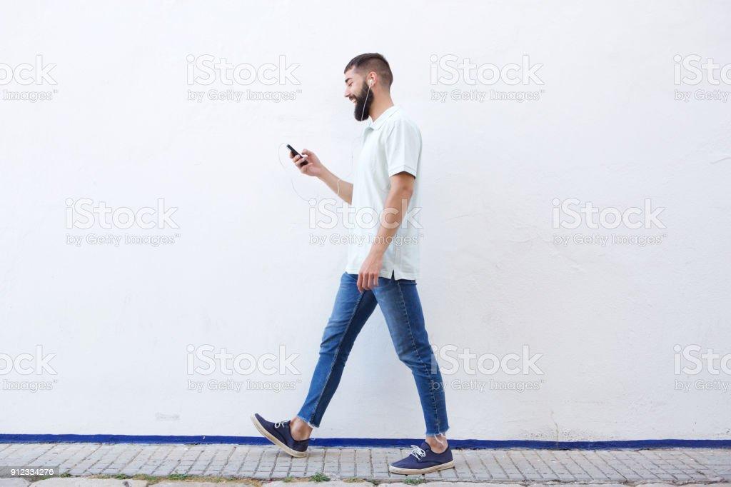 Homme de pleine longueur à pied et la tenue de téléphone mobile avec un casque - Photo