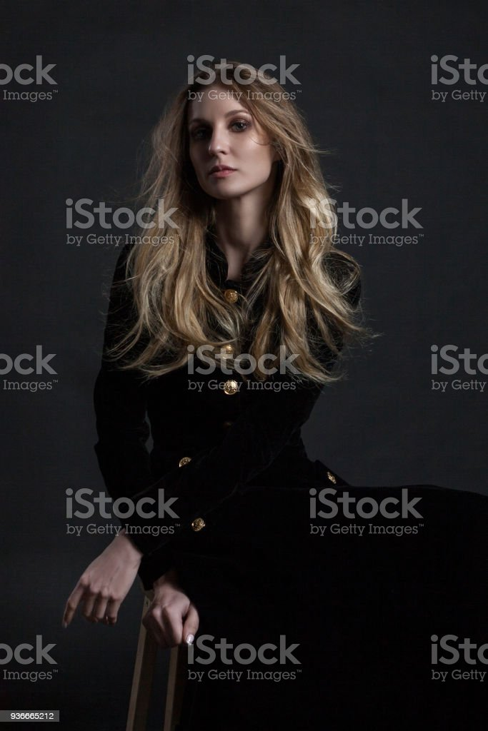 1f4949ad010 Voller Länge Modell im schwarzen Kleid posiert sitzend auf dunklem  Hintergrund Lizenzfreies stock-foto