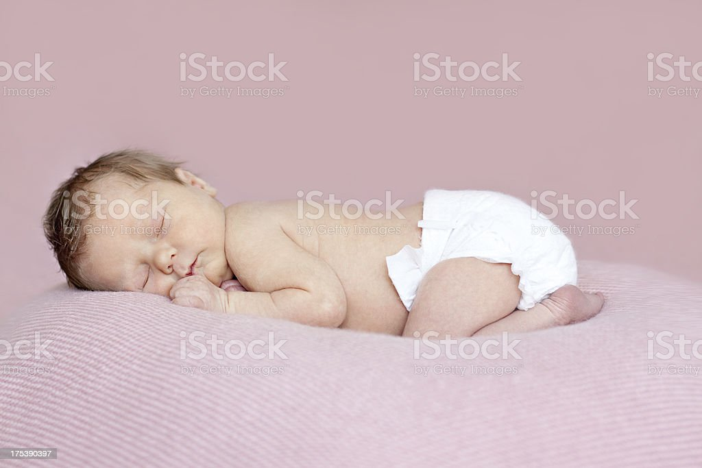Full length newborn baby girl asleep on tummy. Pink background. stock photo