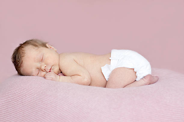 Full length newborn baby girl asleep on tummy. Pink background. stock photo