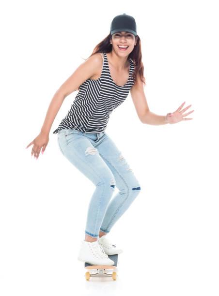 Volle Länge von 20-29 Jahre alt schöne lateinamerikanische und hispanische Ethnie eine junge Frau nur / weiblich / junge Frauen Skateboard / Skateboarding / Skaten vor weißem Hintergrund tragen Jeans / Tank-Top / Mütze / Hut – Foto