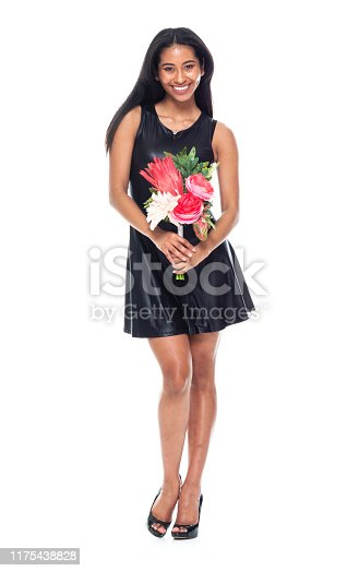 Full length of 20-29 years old beautiful latin american and hispanic ethnicity young women / female in front of white background who is smiling / happy / cheerful / cool attitude and holding flower
