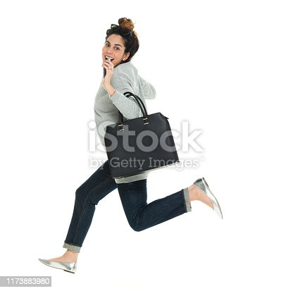 Full length of 30-39 years old adult beautiful puerto rican ethnicity / latin american and hispanic ethnicity female / young women / one young woman only jumping / mid-air in front of white background wearing sweater / jeans / sunglasses who is smiling / happy / cheerful / joy / excited / cool attitude and holding purse / mobile phone / using smart phone