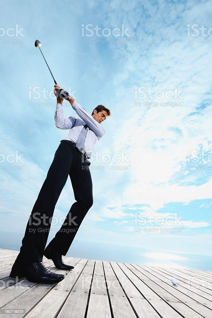 Full length of a businessman playing golf royalty-free stock photo