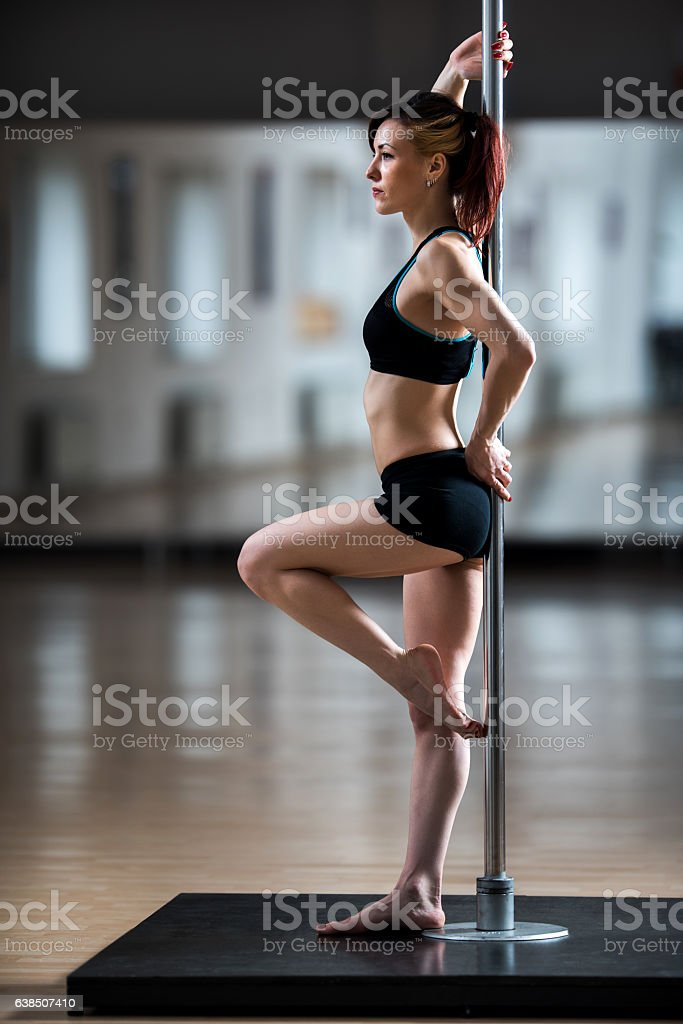 Full length of a pole dancer in a studio. stock photo