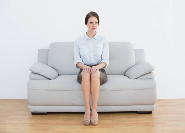 ソファの上深刻な身なりの女性の完全な長さ ストックフォト