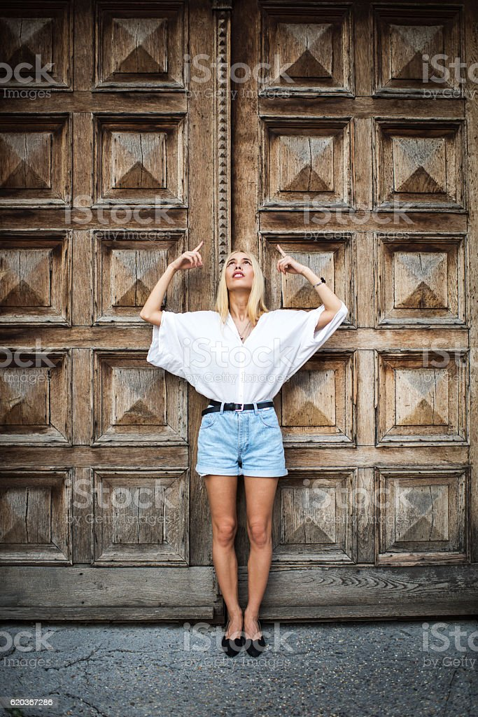 Full length of a woman pointing up against the door. zbiór zdjęć royalty-free