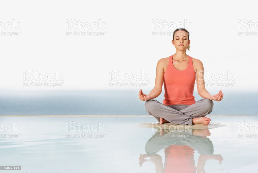 Full length of a young lady meditating outdoors royalty-free stock photo