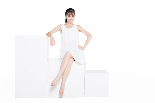 full length of an elegant asian woman sitting over white background stock photo