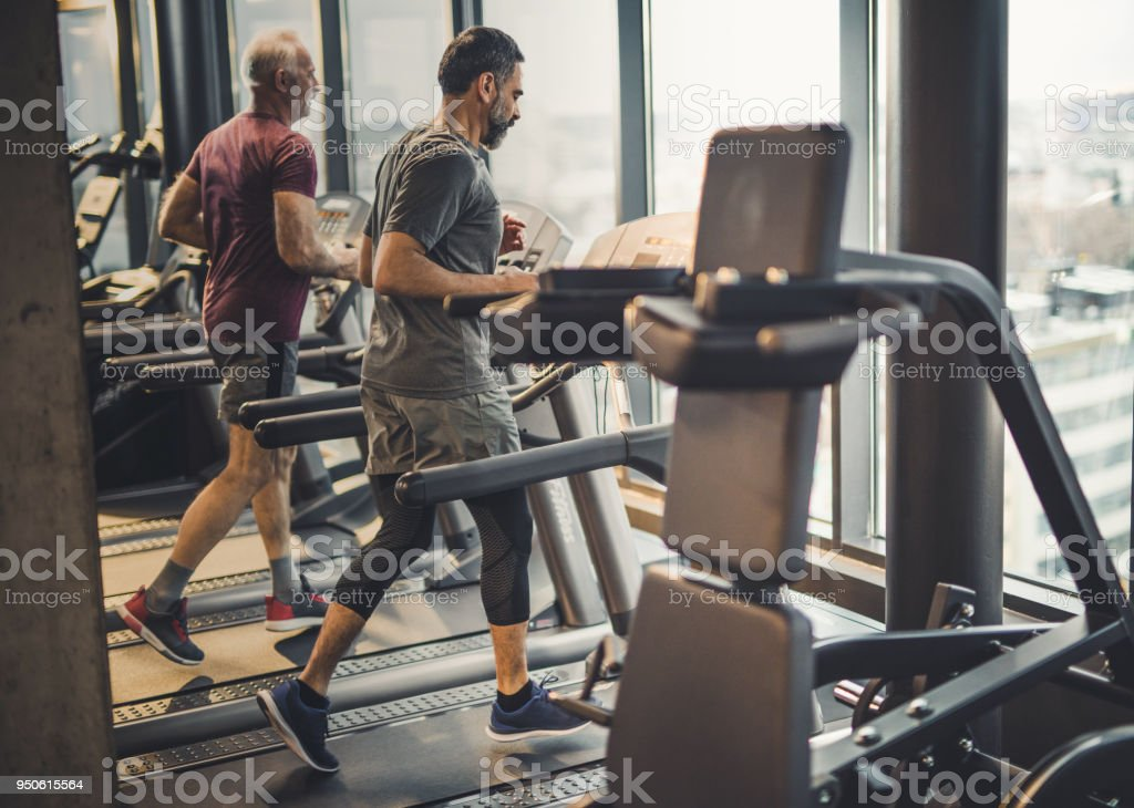 Full length of athletic senior men jogging on treadmills in a health club. stock photo
