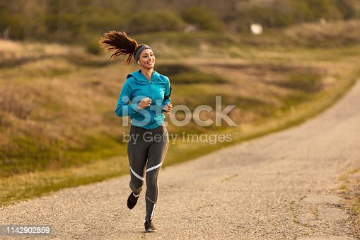 1142900322 istock photo Full length of athletic woman running on the road. 1142902859