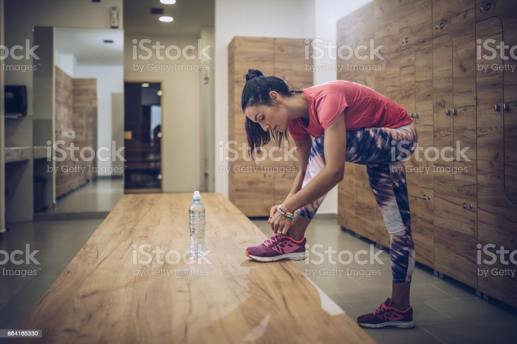 Full length of athletic woman tying shoelaces in dressing room. royalty-free stock photo
