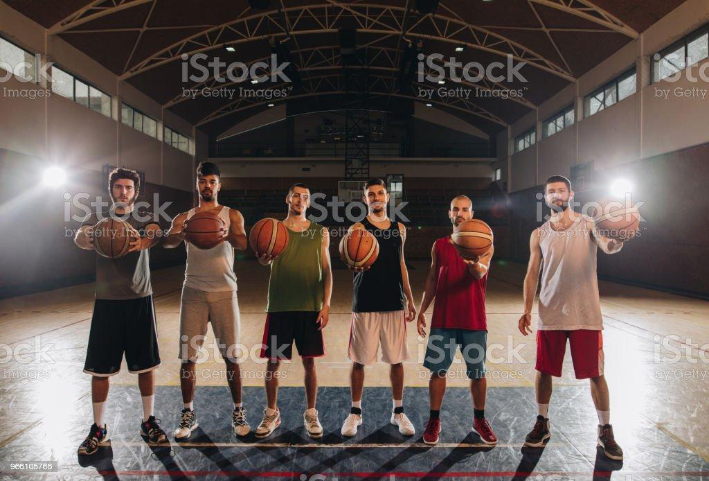 Full längd av basketspelare med bollar på domstolen. - Royaltyfri Afroamerikanskt ursprung Bildbanksbilder