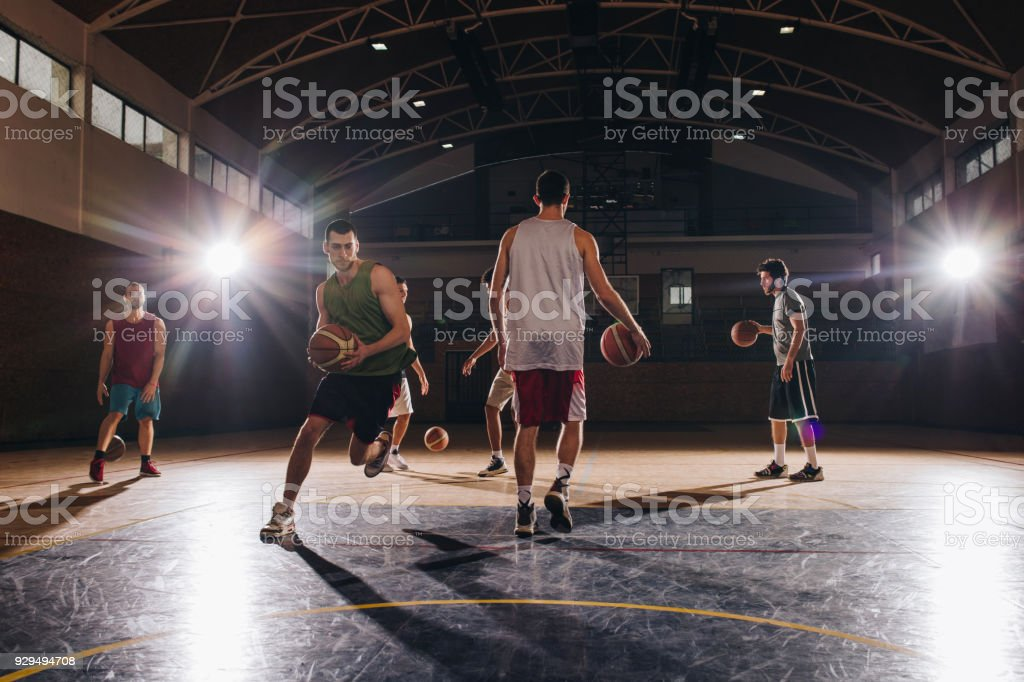 Group of young basketball players exercising with balls on a sports...