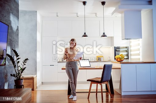 istock Full length of beautiful caucasian blond young woman leaning on dining table, holding paperwork and using smart phone. On table are papers and laptop. 1184412555