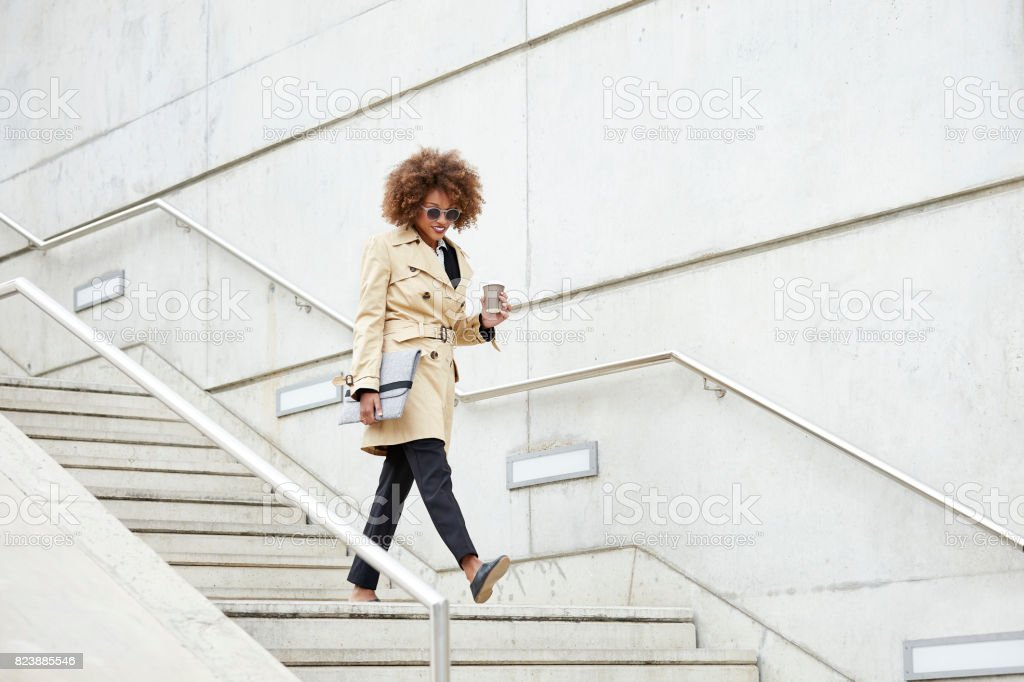 Full length of businesswoman moving down steps stock photo