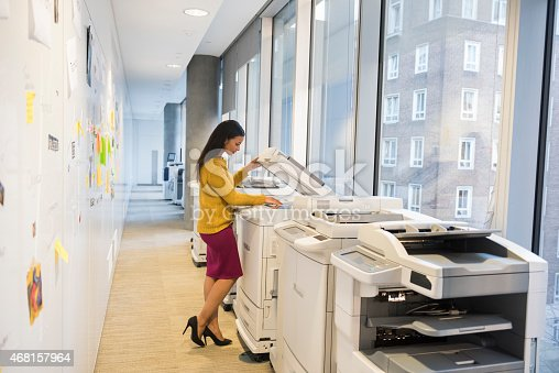 A full length photo of beautiful businesswoman using computer printer. Side view of professional photocopying. Copy machines are found near windows, in a brightly lit modern office alley.