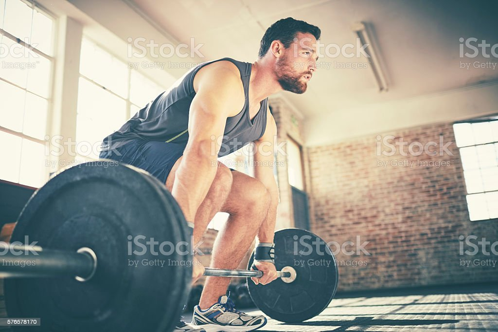Full length of confident man dead lifting barbell in gym - foto de stock