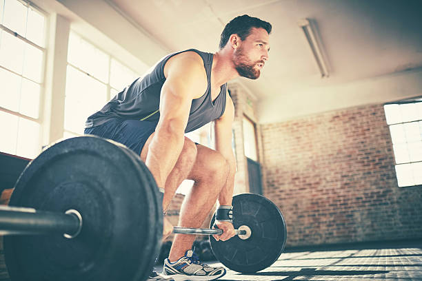 Full length of confident man dead lifting barbell in gym – Foto