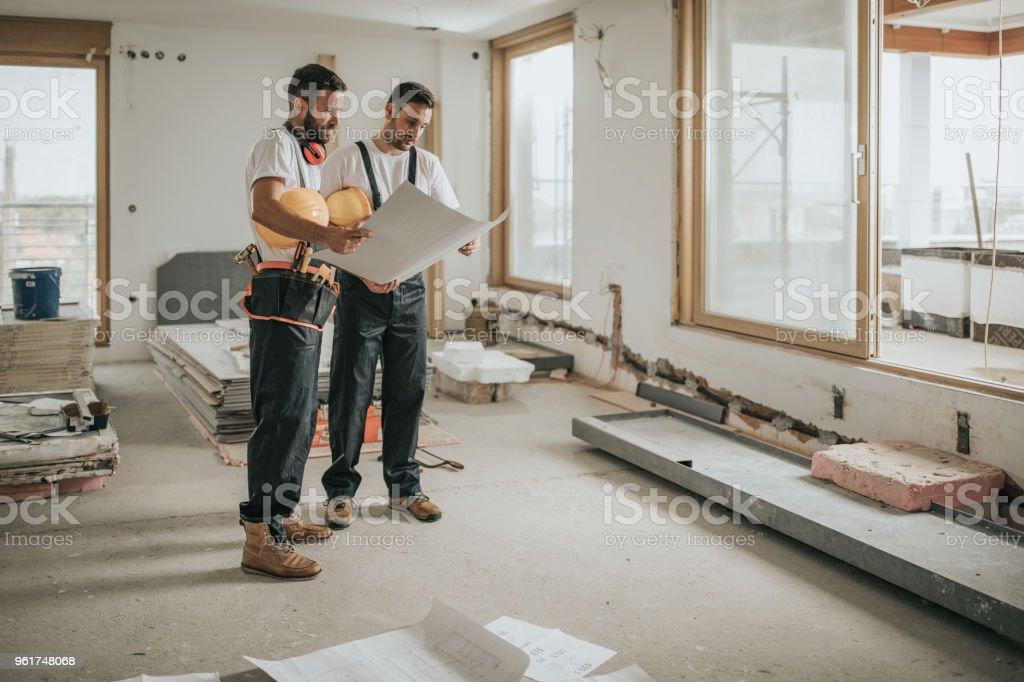 Volledige lengte van de werknemers in de bouw analyseren blauwdrukken in het appartement. - Royalty-free Alleen mannen Stockfoto
