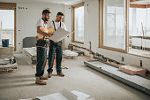 Full length of construction workers analyzing blueprints in the apartment.