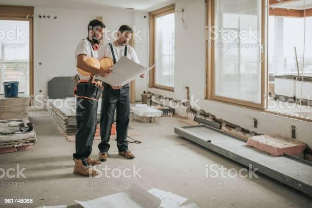 Volledige Lengte Van De Werknemers In De Bouw Analyseren Blauwdrukken In Het Appartement Stockfoto en meer beelden van Alleen mannen