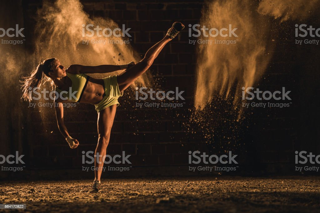 Full length of determined athlete on a kick-boxing training. stock photo