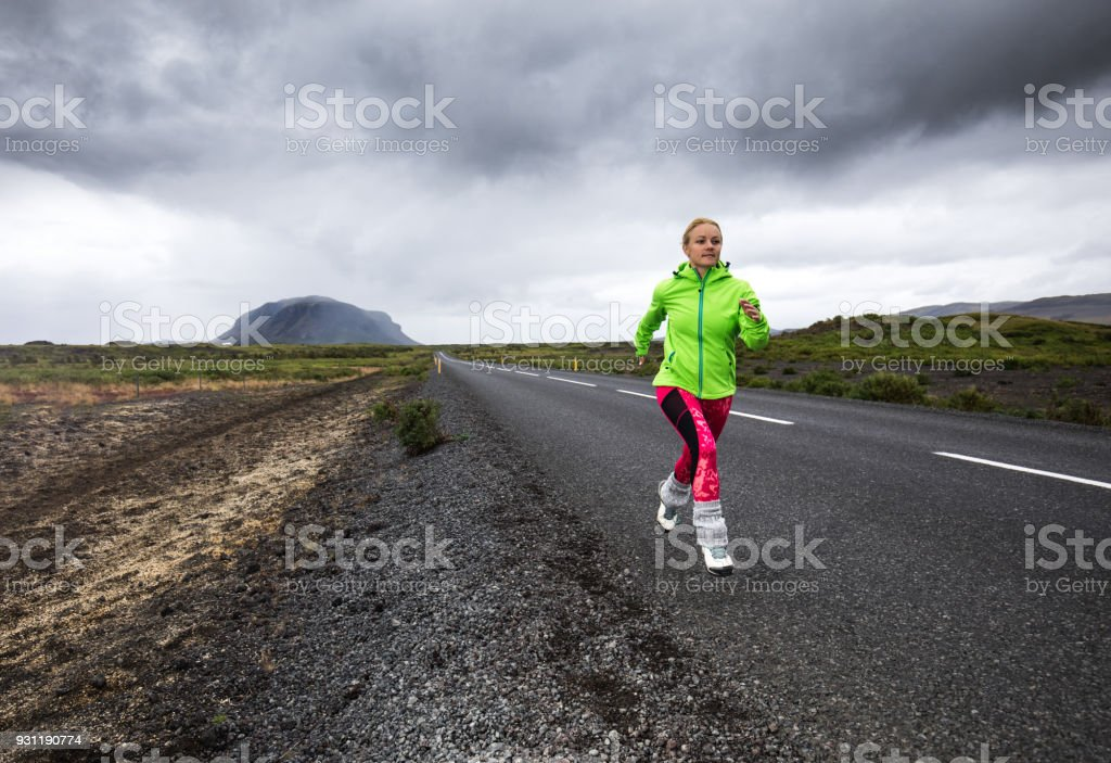 Full length of determined athletic woman running on the road. stock photo