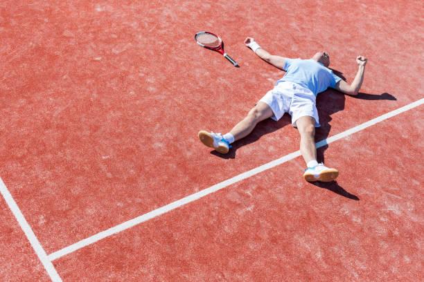 Longitud completa de hombre maduro decepcionado acostado por la raqueta de tenis en la cancha durante el verano - foto de stock
