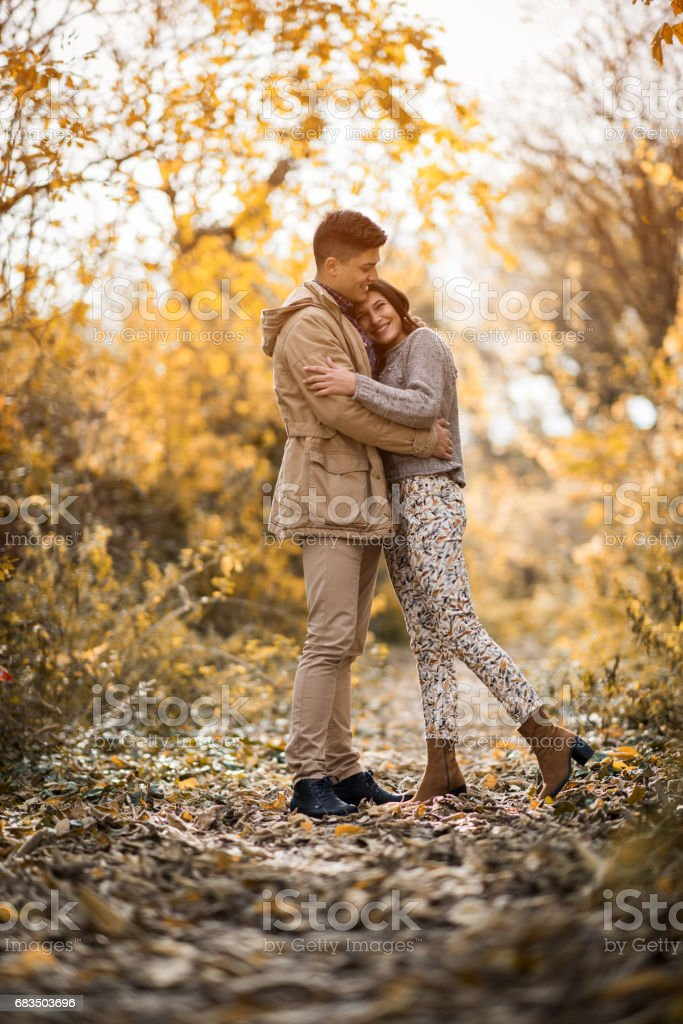 Full length of embraced couple spending an autumn day in forest. stock photo