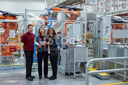 istock Full length of engineers looking away in car plant 1127293047