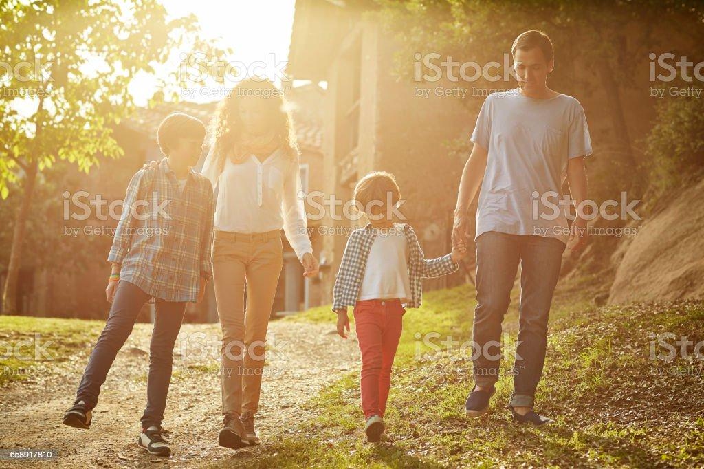 Full length of family walking against houses stock photo