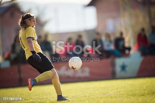 Teenage soccer goalie kicking the ball on a sports training at stadium. There are people in the background.