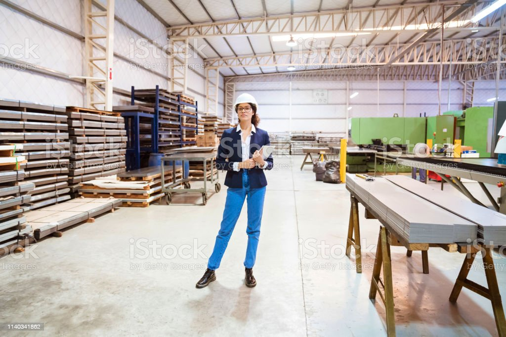 Full length of female manager standing in factory Full length portrait of manager standing in factory. Female inspector is holding digital tablet in warehouse. She is on visit in manufacturing company. 30-34 Years Stock Photo