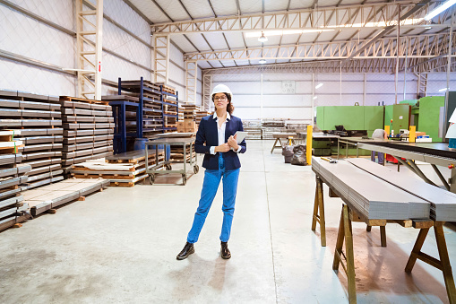 Full Length Of Female Manager Standing In Factory Stock Photo - Download Image Now