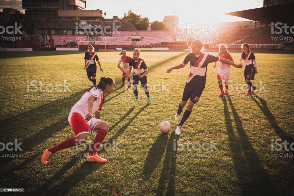 Volle Länge des weiblichen Fußballer in Aktion auf ein Match bei Sonnenuntergang. – Foto