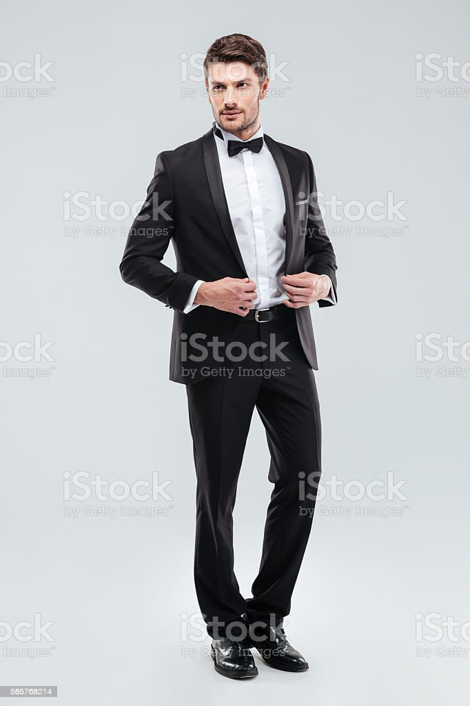 Full length of handsome young man in tuxedo with bowtie stock photo