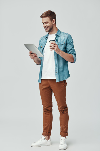 istock Full length of handsome young man smiling and using digital tablet while standing against grey background 1170874296