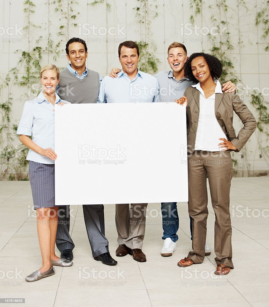 Full length of happy business colleagues holding a placard royalty-free stock photo