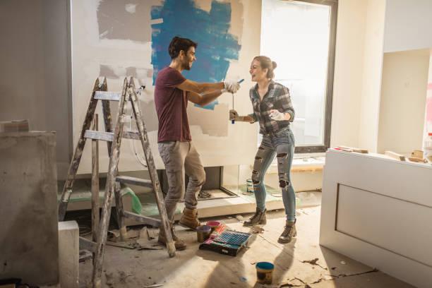 Duvarlarını boyarken eğlenen mutlu çiftin tam boy. stok fotoğrafı