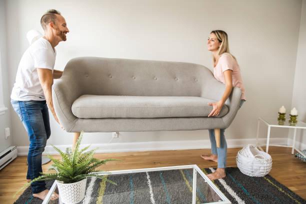 toute la longueur du couple heureux, plaçant le canapé dans le salon de la maison neuve - ameublement photos et images de collection