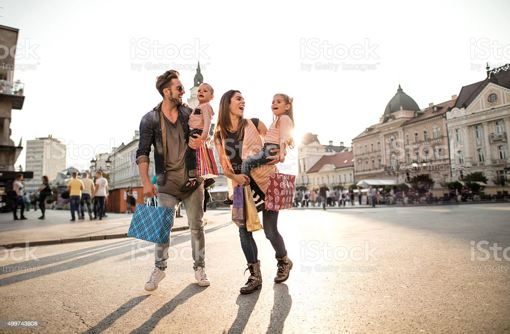 Full length of happy family shopping in the city. stock photo