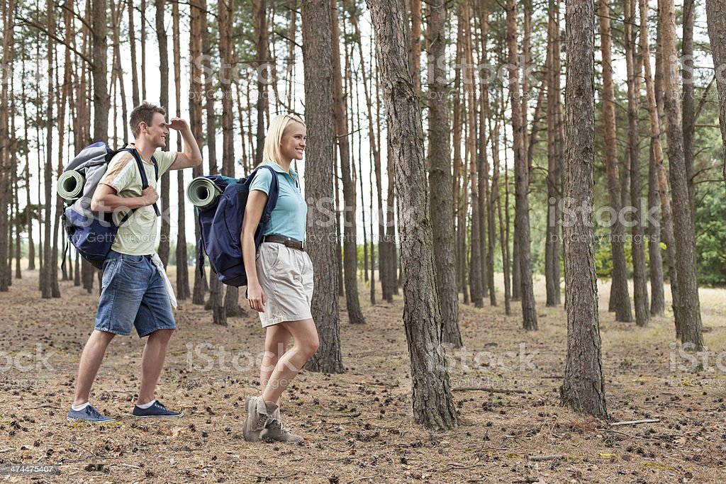Full length of happy young couple hiking in forest royalty-free stock photo