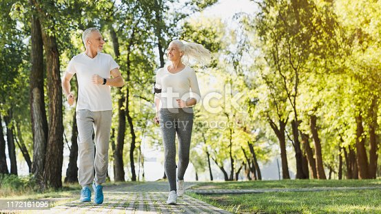 942580016istockphoto Full length of healthy mature couple jogging in park at early morning 1172161095