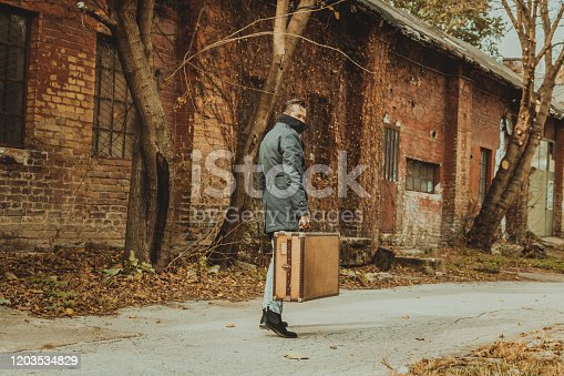 Full length of man in coat carrying suitcase while walking on the street and looking at camera.