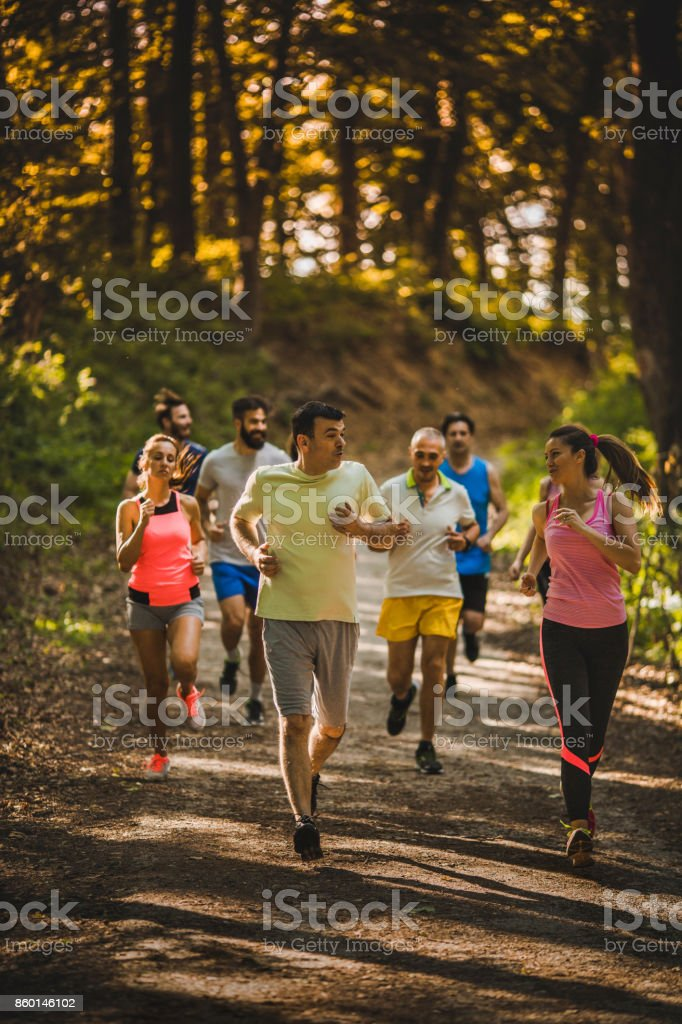 Full length of marathon runners communicating during a race. stock photo